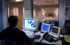Image: Technician watches a patient go through a MRI machine